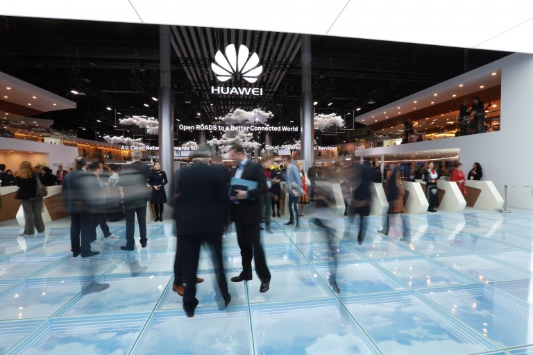 People gather around a Huawei booth at the Mobile World Congress.