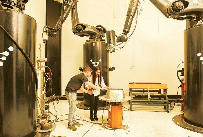 Two people working alongside 3D printer robot arms