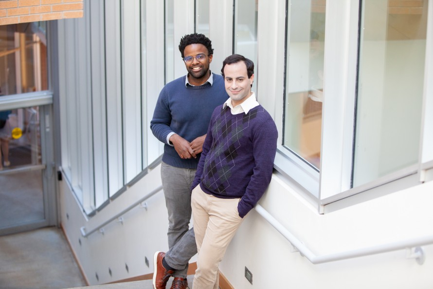 Michael Carbin and Jonathan Frankle, the authors of the paper, pose on a staircase.