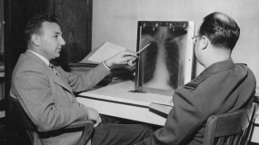 Black and white photo of two men looking at chest x-rays