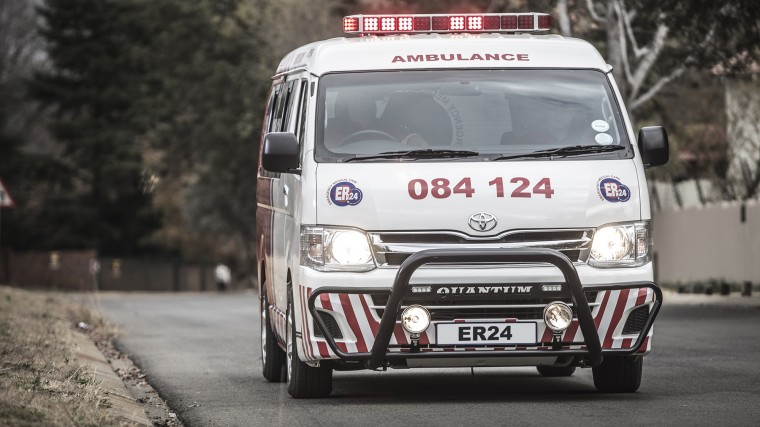A photo of an ambulance with its lights on driving down a street