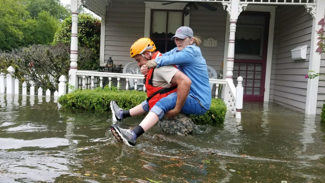 A member of the Texas National Guard carries a woman passed a flood house