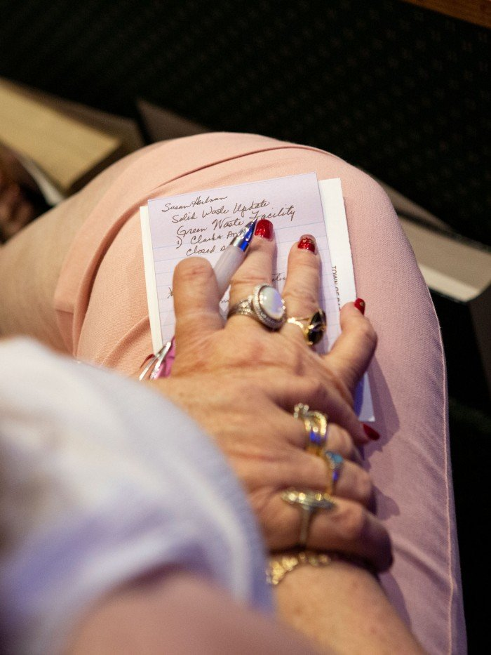 Photograph of a woman's hands taking notes about rebuilding at the city council meeting