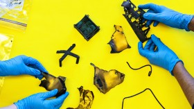 Photograph of two people wearing gloves examining space debris on a yellow table top