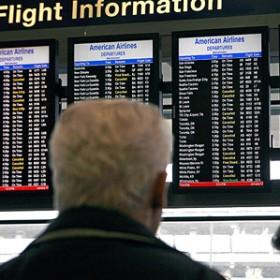 man looks at flight info on airport monitor