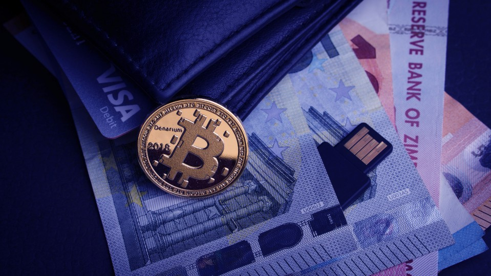 A physical representation of a bitcoin rests on a wallet that also contains a Visa card and paper banknotes from several countries.