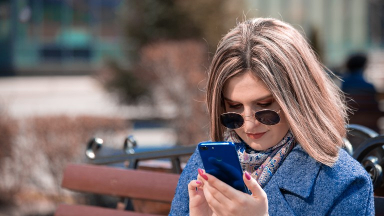 woman looking at phone on park bench