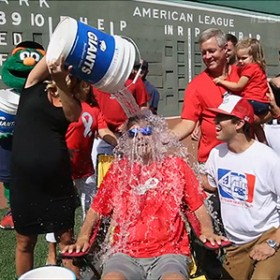 man getting cooler of ice water poured over his head with onlookers