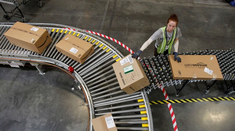 An Amazon worker putting packages on a conveyor belt