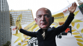 A person wearing a giant Jeff Bezos mask stands in front of a protest.