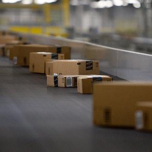boxes travel along a conveyer in Amazon fulfillment center