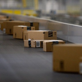boxes travel along a conveyer in Amazon fulfillment center
