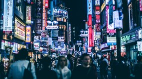 People walking on a busy commercial street at night in Shibuya, Japan.