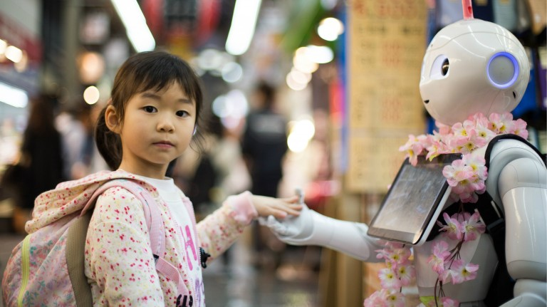Little girl holding hands with a white robot about her size