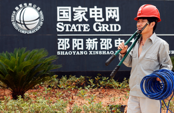 photograph of A electrician stands in front of a State Grid branch in China's Hunan province in 2011.an
