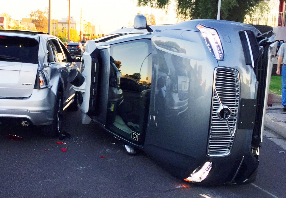 An image showing the aftermath of a self-driving car accident, with an uber vehicle on its side