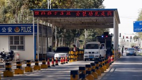 Uighur drivers have their vehicles checked at a police check point in Hotan