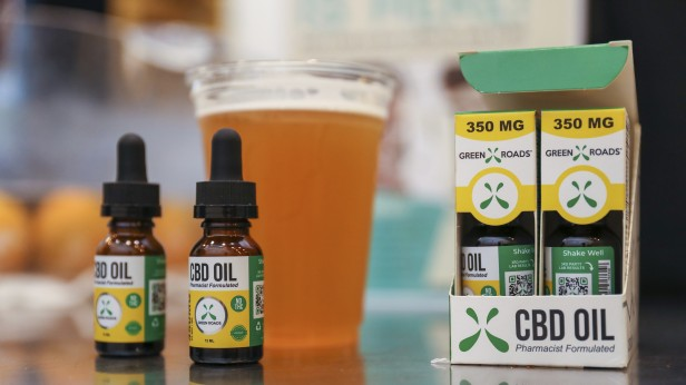 Photograph of CBD oil as well as a beer