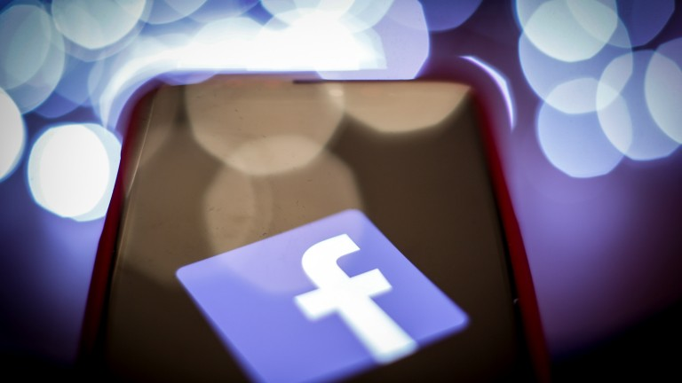 Conceptual image of Facebook's logo and a mobile phone