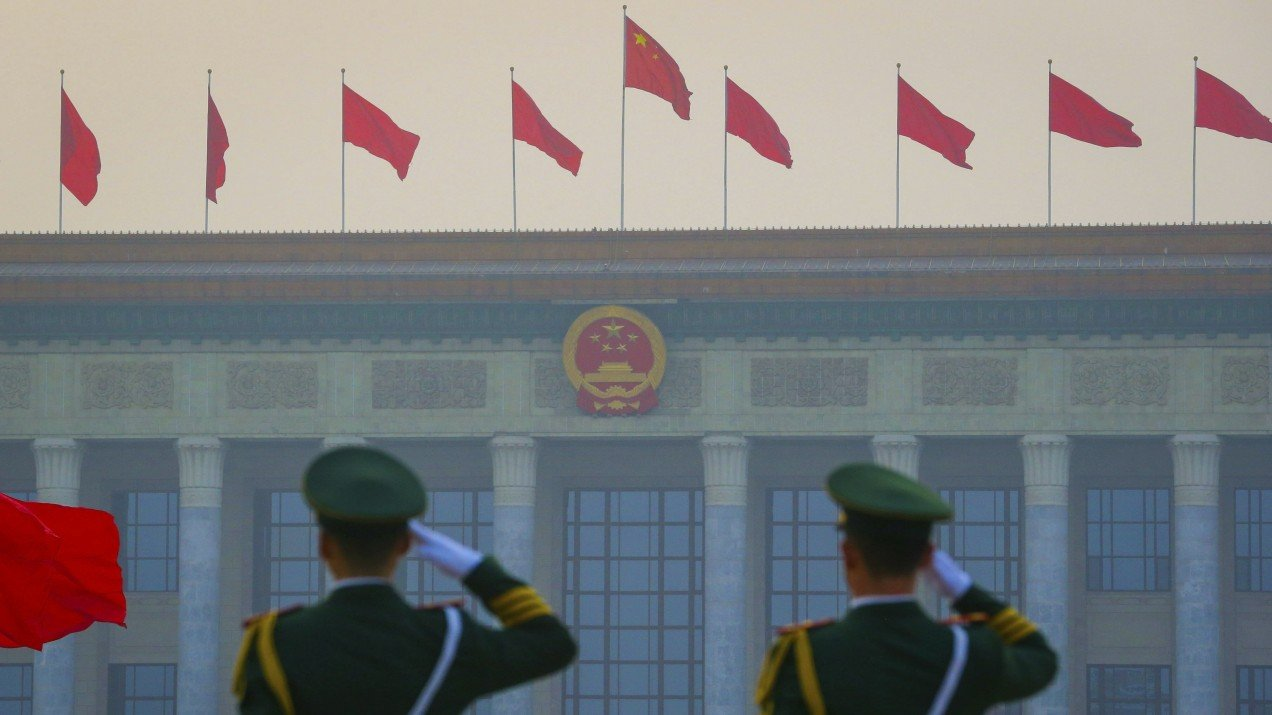 Chinese paramilitary armed policemen salute as red flags flutter in front of the Great Hall of the People in Beijing.