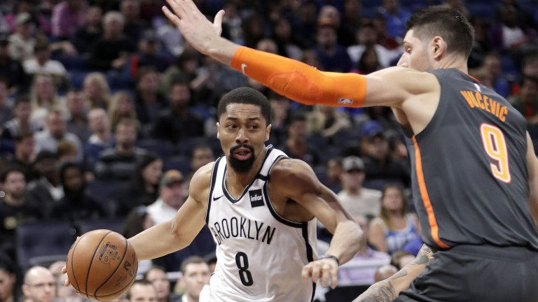 Brooklyn Nets guard Spencer Dinwiddie dribbling past a defender.