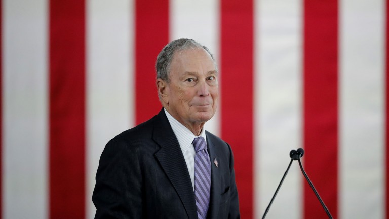 Michael Bloomberg, during a speaking event, with the stripes of the American flag in the background.