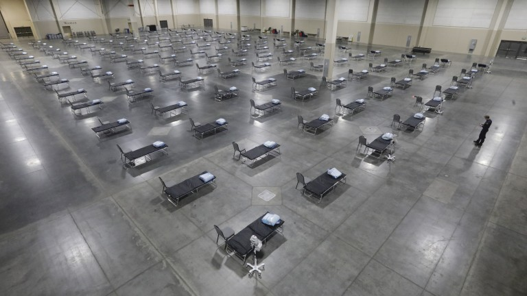 Rows and rows of hospital beds in a convention center, set up as an overflow room for non-coronavirus patients.