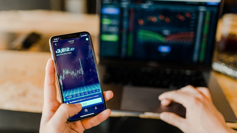 A person holding a smartphone with a cryptocurrency trading app open. A laptop sits on the desk in the background.