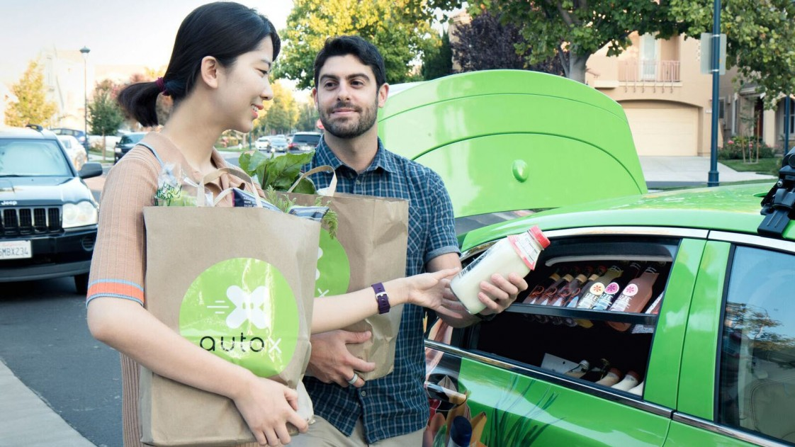 People select healthy snacks from the backseat of a self-driving car developed by the startup AutoX.