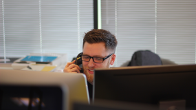 Image of man on a phone in an office.