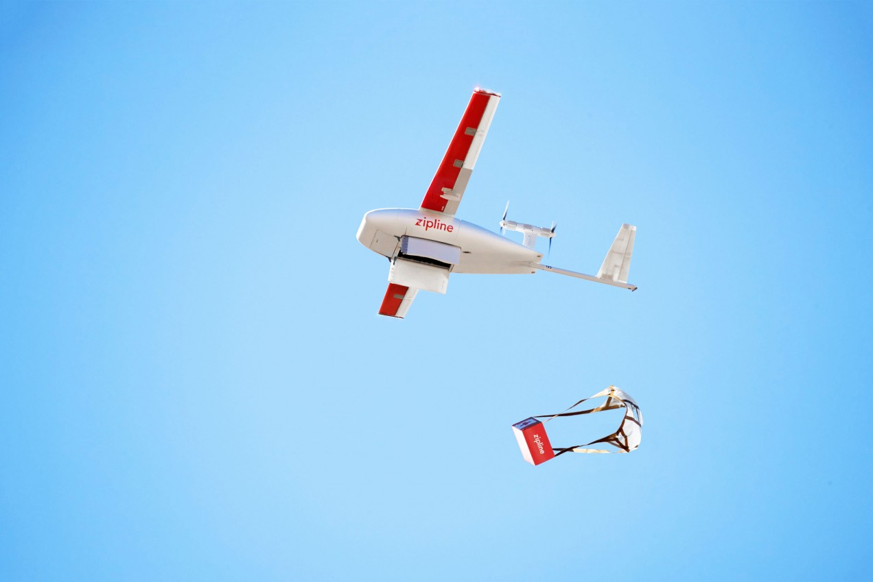 An image of a Zipline airplane dropping a parachuted box