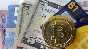 """A metal token made to look like a """"bitcoin,"""" with regular fiat currency underneath"""