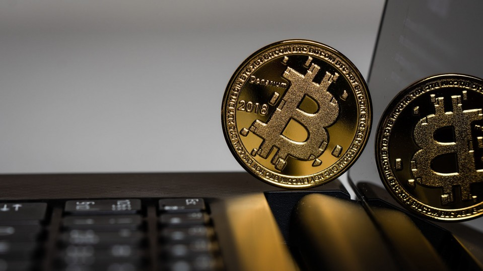 A physical representation of a Bitcoin leaning against a laptop screen