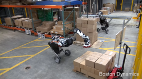 Two robots in a warehouse moving boxes from pallets to a conveyor belt