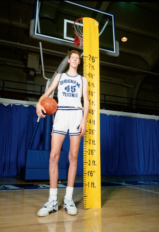 Photo of man in basketball uniform, on basketball court, standing beside ruler reading 7'6""