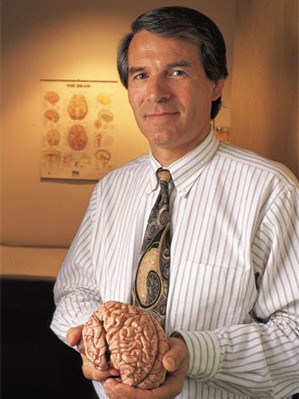An image of a man holding a model of a human brain