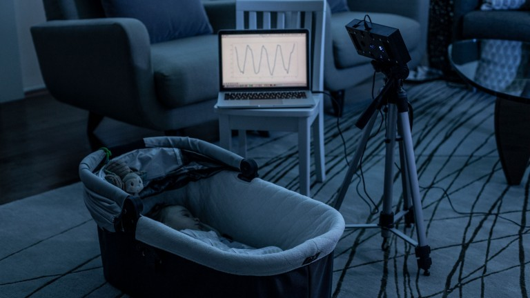 A baby sleeping in a cot has their breathing monitored remotely