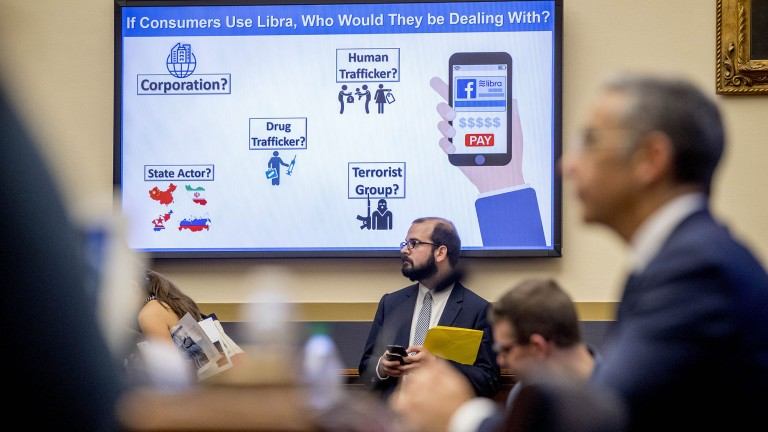 A big screen in the Congressional hearing room poses questions about Facebook's Libra.