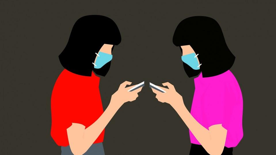 Women wearing face masks checking their phones