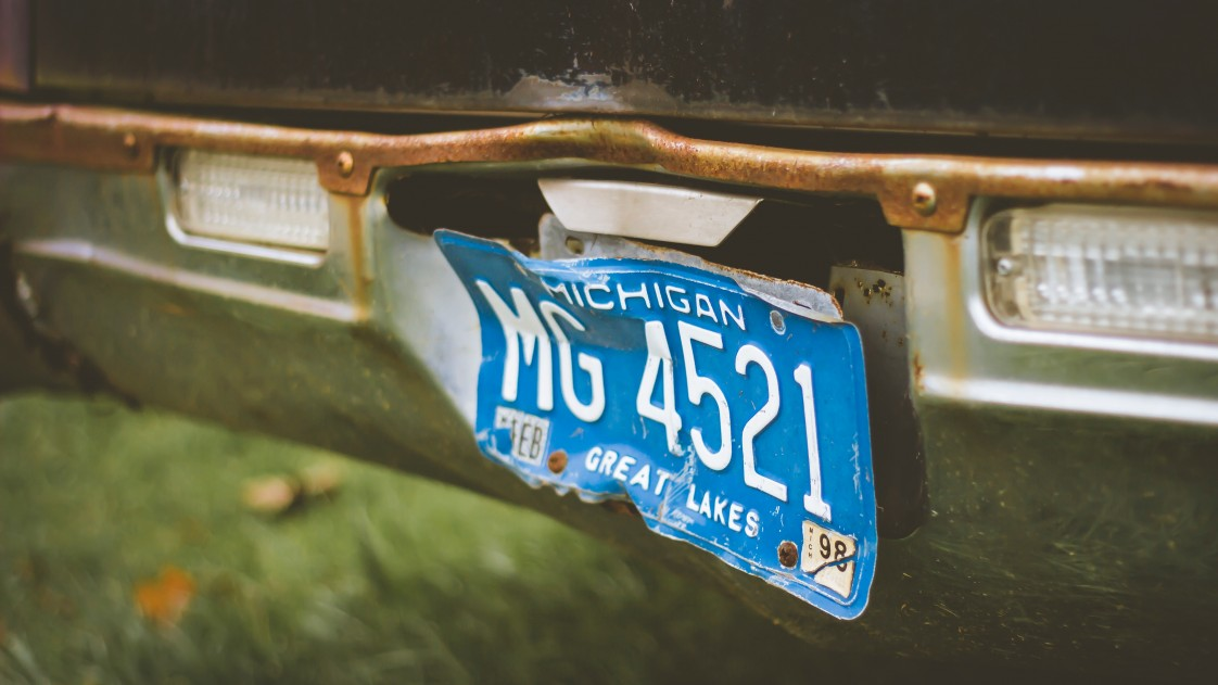 Photo of a Michigan license plate a little dinged up
