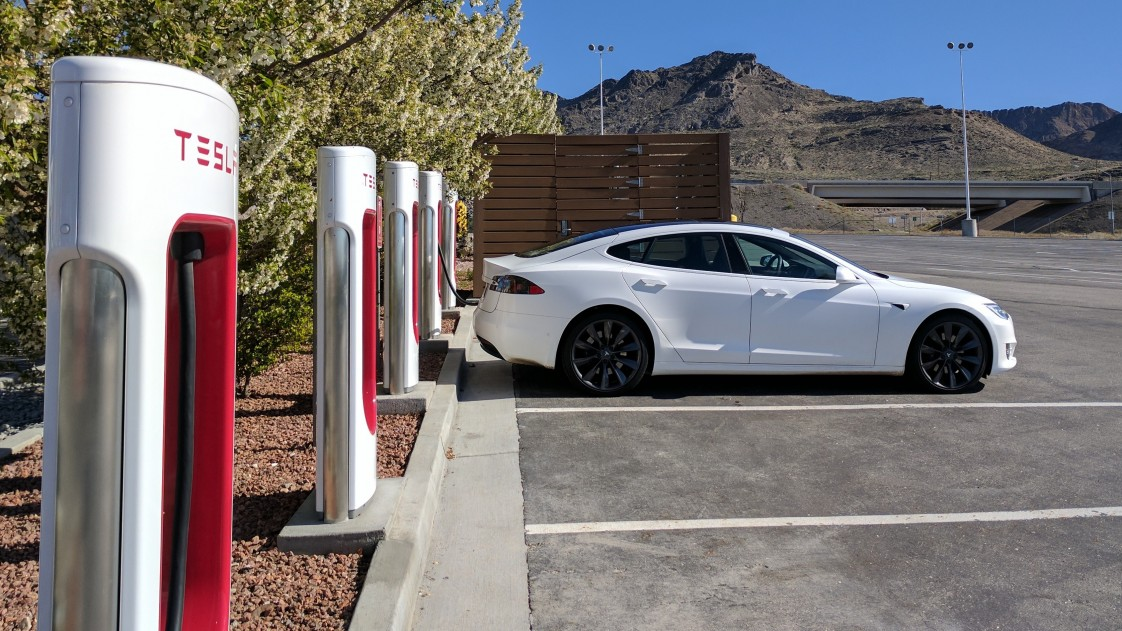 A Tesla car charging at a supercharger station