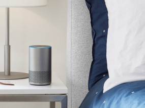 An Amazon Echo device beside a bed