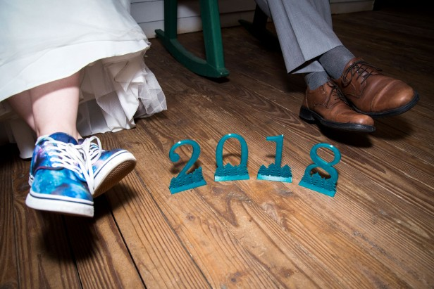 "Erin and groom Alex's feet beside 3-D printed numbers ""2018"""