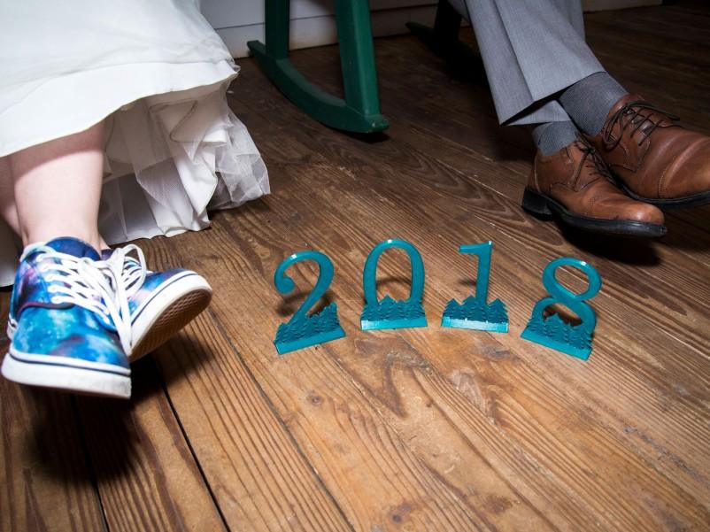 """Erin and groom Alex's feet beside 3-D printed numbers """"2018"""""""