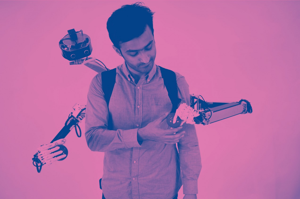 Image of man exchanging a ball with a hand of the robotic-armed backpack.