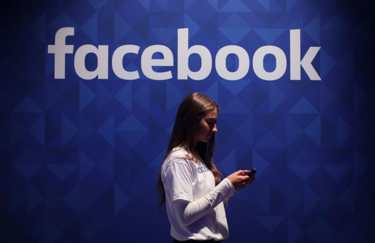 A woman looking at her smartphone beneath Facebook's logo