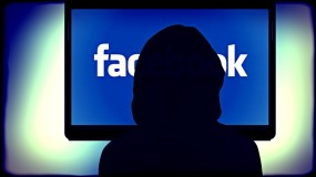 A figure wearing a black hoody in front of a screen with Facebook's logo on it
