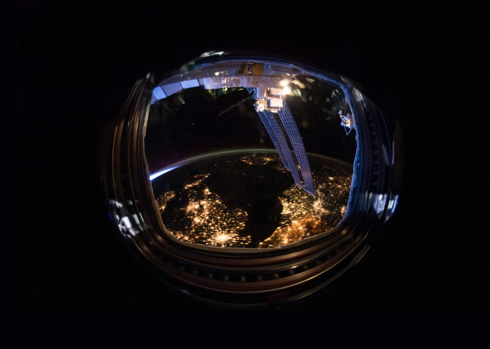 An astronaut helmet reflecting a light-filled earth