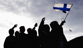 Silhouettes of people raising Finland's flag.