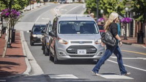 A pedestrian crosses in front of a self-driving car